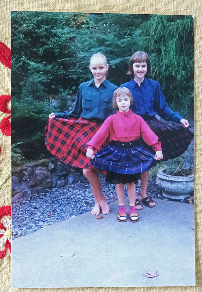 three little girls wearing plaid skirts