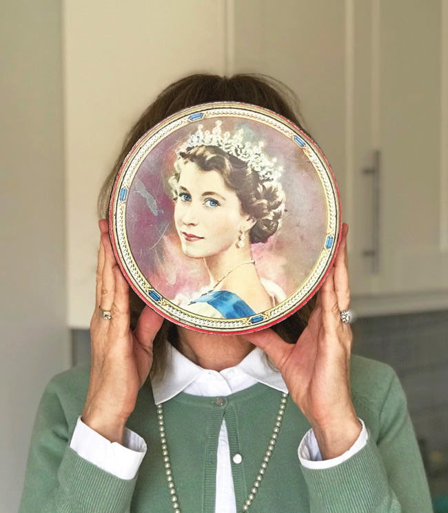 Woman holds vintage Queen Elizabeth cookie tin in front of face