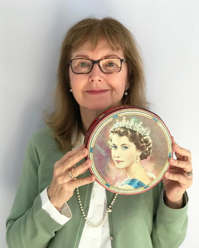 Author Elinor Florence holding vintage Queen Elizabeth cookie tin