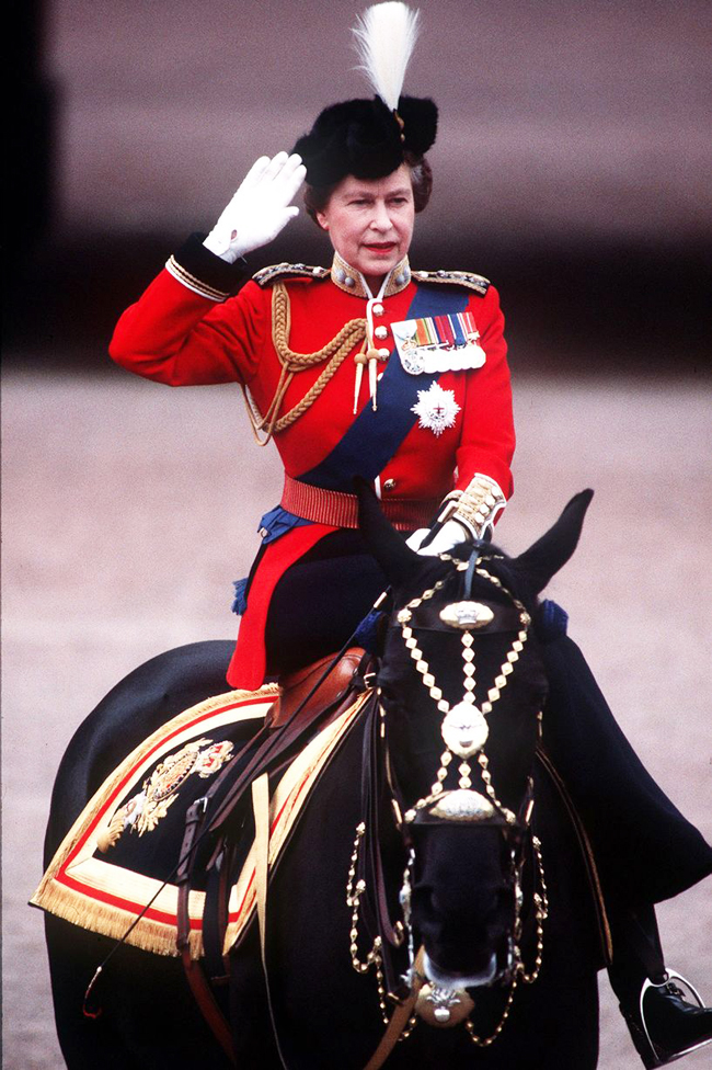 Queen Elizabeth in red uniform seated on black horse, saluting