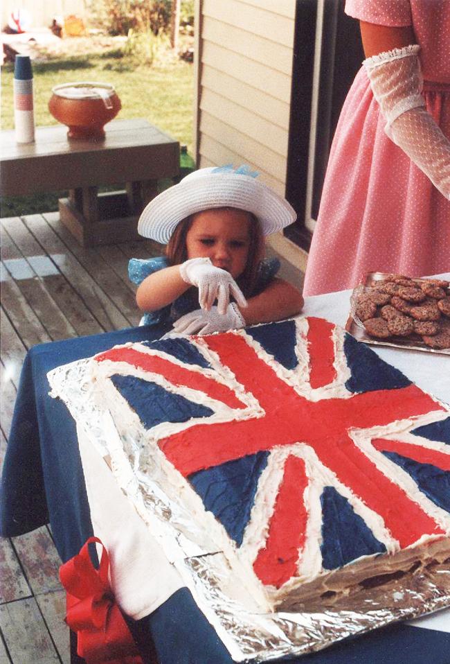 Little girl pokes finger into Union Jack cake