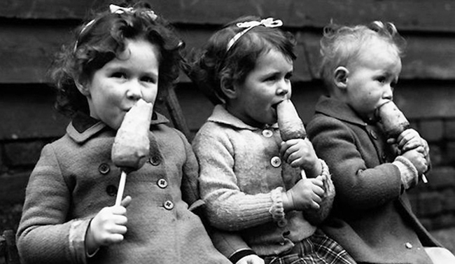 three young children in wartime eating carrots on sticks